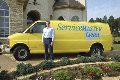 A ServiceMaster technician standing in front of a branded vehicle