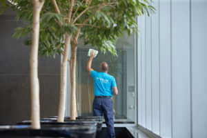 A ServiceMaster technician cleaning a large glass window