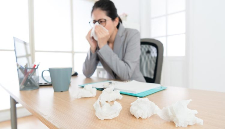 Woman sneezing at a desk with dirty tissues