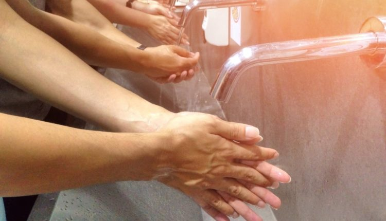 People washing their hands at a communal sink
