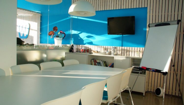 Office conference room with a table, chairs and a tv screen on a blue wall