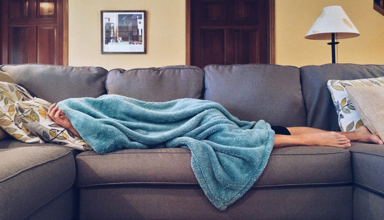 Sick employee lying on the sofa at home